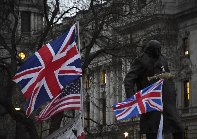 Brexit supporters hold British and US flags in front of the Statue of Winston Churchill during a rally in London, Friday, Jan. 31, 2020.