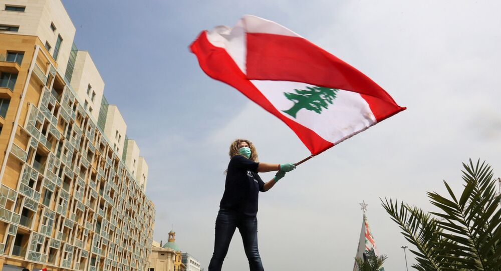 An anti-government demonstrator holds a Lebanese flag as she stands on top of her car, during a countrywide lockdown to combat the spread of the coronavirus disease (COVID-19), in Beirut, Lebanon April 21, 2020.