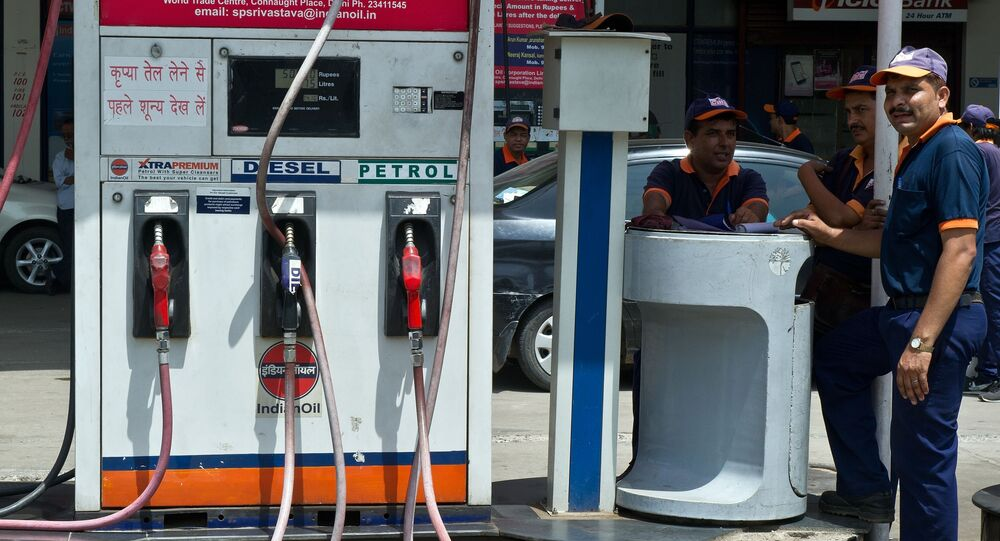 Employees of a petrol pump wait for customers in New Delhi on September 2, 2013. India is considering closing fuel pumps at night as one of a number of austerity measures aimed at cutting its ballooning oil import bills, the oil minister said.