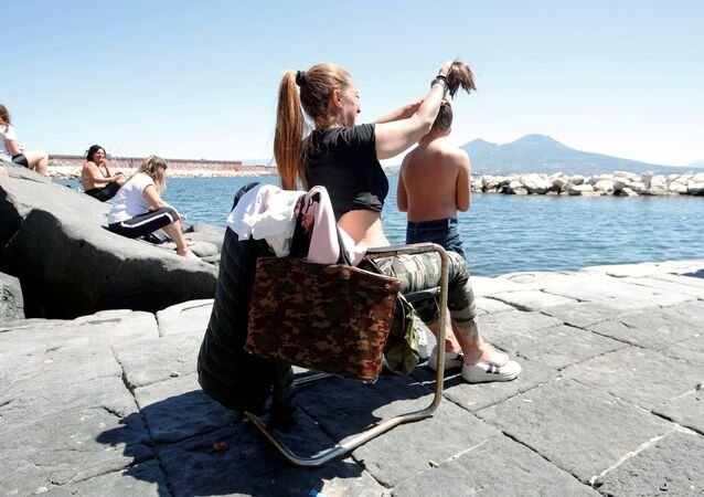 People are seen at the seaside, as Italy begins a staged end to a nationwide lockdown which was put in place due to the spread of the coronavirus disease (COVID-19), in Naples, 4 May 2020.
