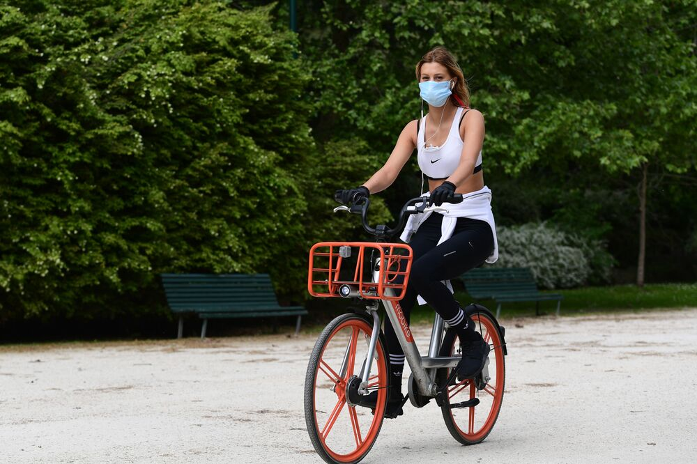 A woman rides a rental bicycle across Parco Sempione Park on 4 May 2020 in Milan as Italy starts to ease its COVID-19 lockdown. Stir-crazy Italians will be free to stroll and visit relatives for the first time in nine weeks on 4 May 2020 as Europe's hardest-hit country  incrementally softens the world's longest nationwide coronavirus lockdown.
