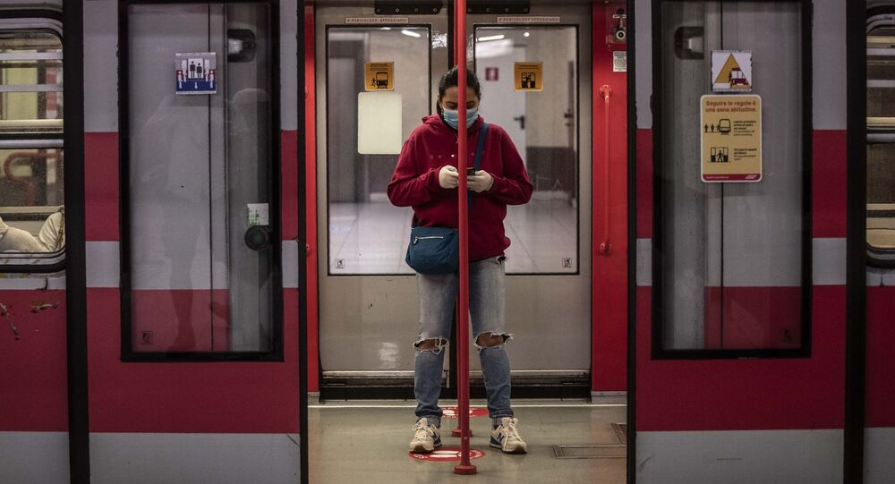 A woman stands in a subway wagon at a stop, in Milan
