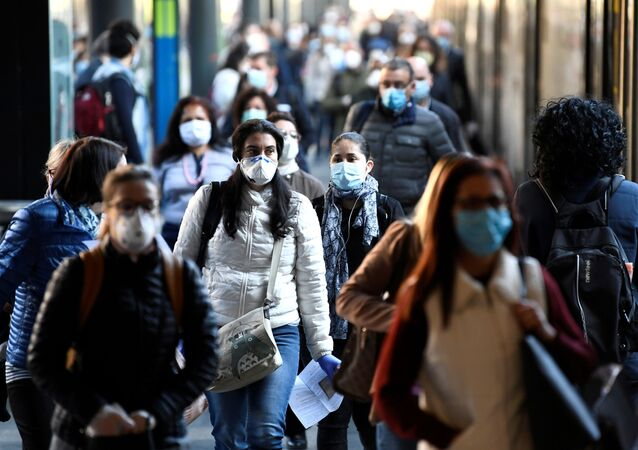 People wearing face masks arrive at the Cadorna railway station