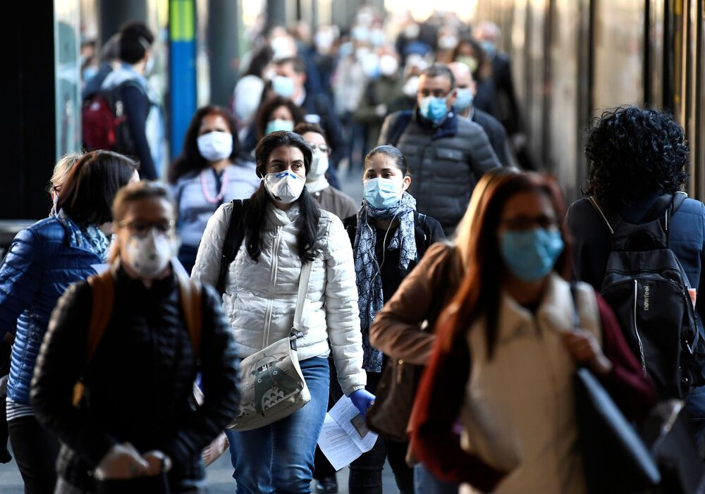 People wearing face masks arrive at the Cadorna railway station, as Italy begins a staged end to a nationwide lockdown due to the spread of the coronavirus disease (COVID-19), in Milan, Italy 4 May 2020.