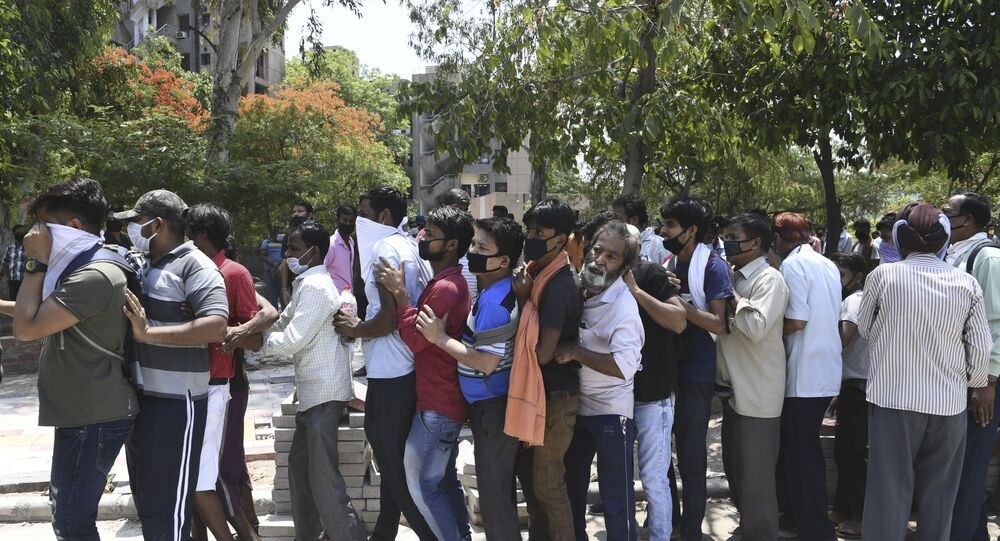 People queue to buy alcohol outside a liquor shop after the government eased a nationwide lockdown imposed as a preventive measure against the spread of the COVID-19 coronavirus in New Delhi on May 5, 2020.