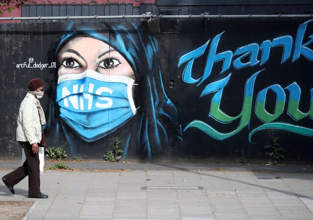 A person wearing a protective face mask walks past the 'NHS Dedication Mural' by The Artful Dodger (A.Dee) in Elephant & Castle, following the outbreak of the coronavirus disease (COVID-19), London, Britain, 5 May 2020