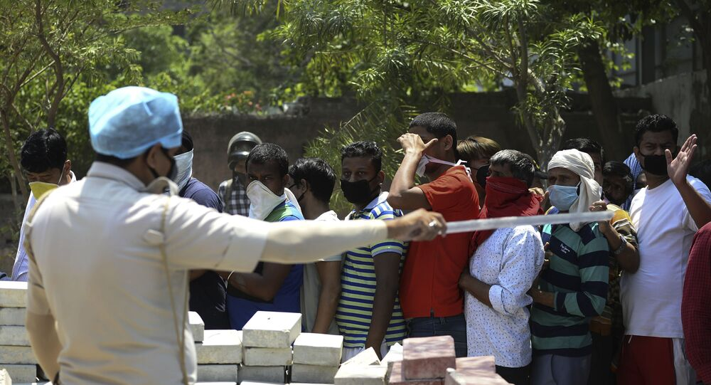 A police personnel gestures to people queueing up to buy alcohol outside a liquor shop after the government eased a nationwide lockdown imposed as a preventive measure against the spread of the COVID-19 coronavirus in New Delhi on May 5, 2020.