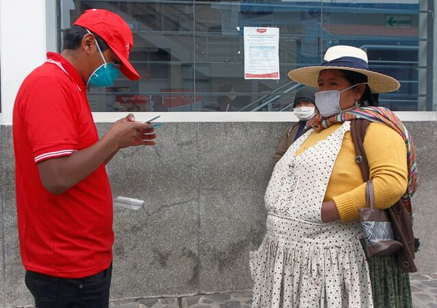 People in the highland city of Puno, close to the border with Bolivia, queue outside a bank on May 4, 2020 to collect the second bonus of 380 soles -about 107 US dollars- of governmental aid to help low income families to stay at home to fight the spread of the new COVID-19 coronavirus.