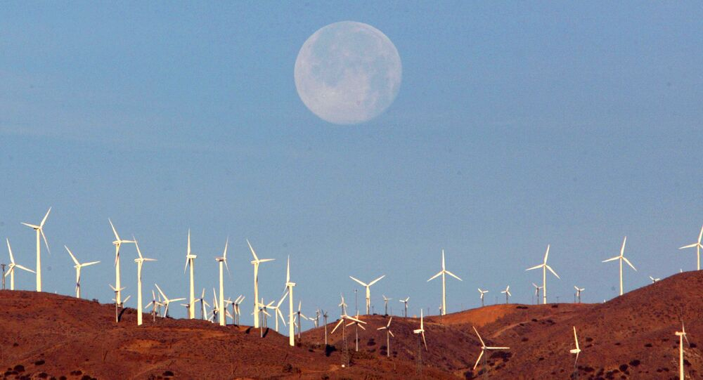 The full moon sets behind a wind farm in the Mojave Desert in California, January 8, 2004.  Picture taken January 8, 2004.