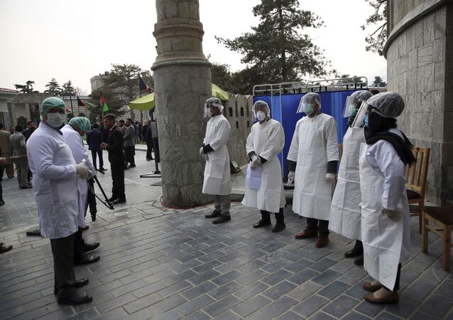 In this Monday, March 9, 2020 file photo, Afghan health workers wait to take the temperature of guests as a precaution for the coronavirus at the entrance gate of the presidential Palace during an inauguration ceremony for Afghan President Ashraf Ghani, in Kabul, Afghanistan.