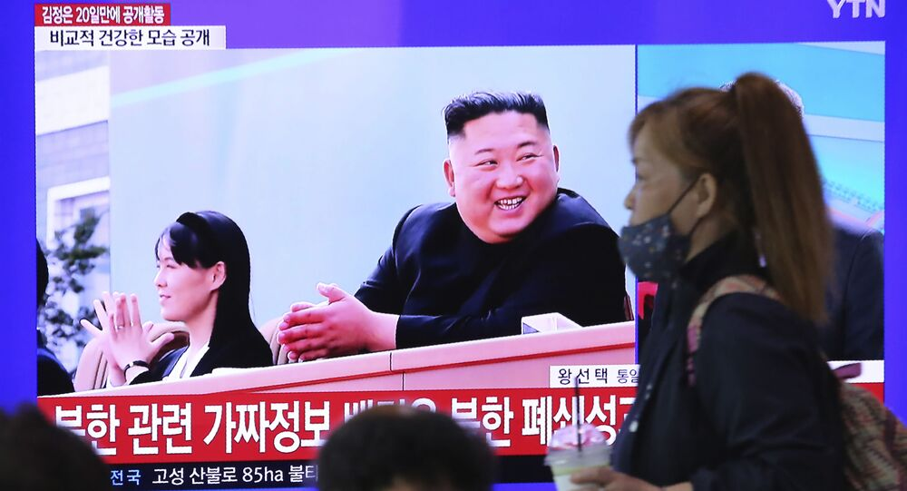 A woman passes by a TV screen showing an image of North Korean leader Kim Jong Un and his sister Kim Yo Jong during a news program at the Seoul Railway Station in Seoul, South Korea, Saturday, May 2, 2020.