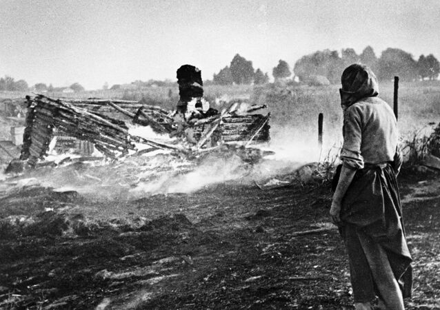 A woman stands next to a burnt house in a village during WW II