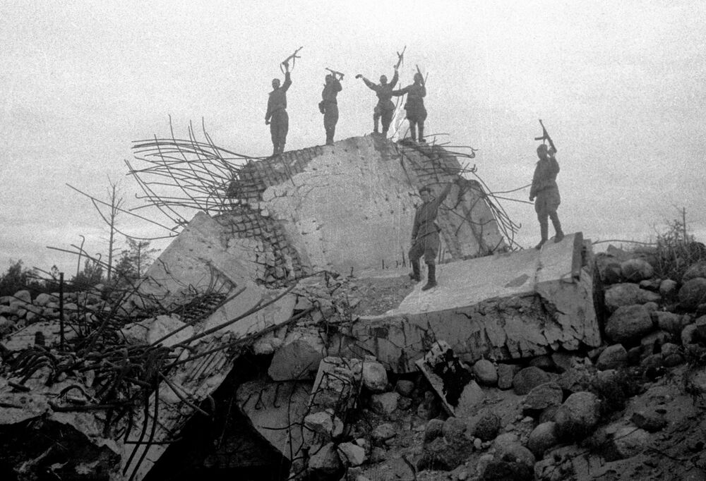 The soldiers stand on the wreckage of one of the German pillboxes blown up by Soviet troops. Leningrad Front.