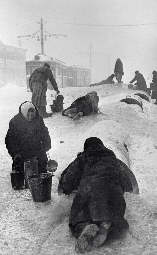 Residents of besieged Leningrad are collecting water from a broken water supply on an icy street.