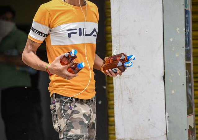A man carries bottles of alcohol bought from a liquor shop after the government eased a nationwide lockdown imposed as a preventive mearure against the COVID-19 coronavirus, in Ghaziabad on May 6, 2020.