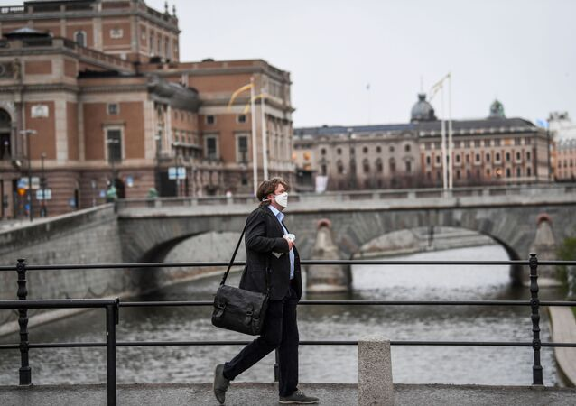A man wearing a protective mask walks past the Royal Swedish Opera, amid the coronavirus disease (COVID-19) outbreak in Stockholm, Sweden, 27 April 2020
