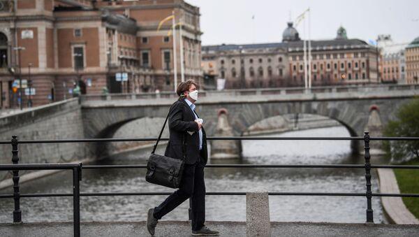 A man wearing a protective mask walks past the Royal Swedish Opera, amid the coronavirus disease (COVID-19) outbreak in Stockholm, Sweden, April 27, 2020 - Sputnik International