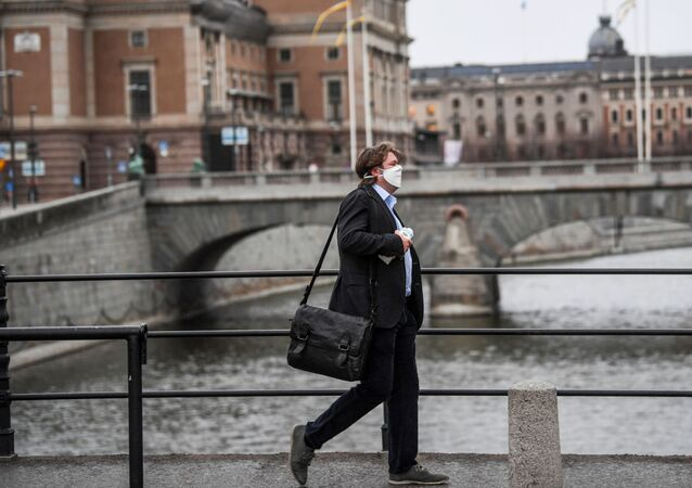 A man wearing a protective mask walks past the Royal Swedish Opera, amid the coronavirus disease (COVID-19) outbreak in Stockholm, Sweden, April 27, 2020