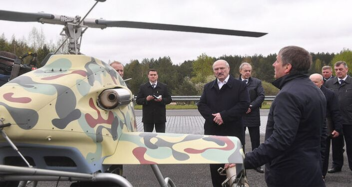 Engineer tells Belarusian President Alexander Lukashenko about a new helicopter drone design.