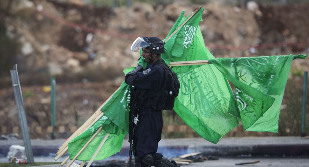 A member of the Israeli security forces carries flags of the Palestinian movement Hamas found at a clashing site near Ramallah, West Bank, Thursday, Oct. 8, 2015
