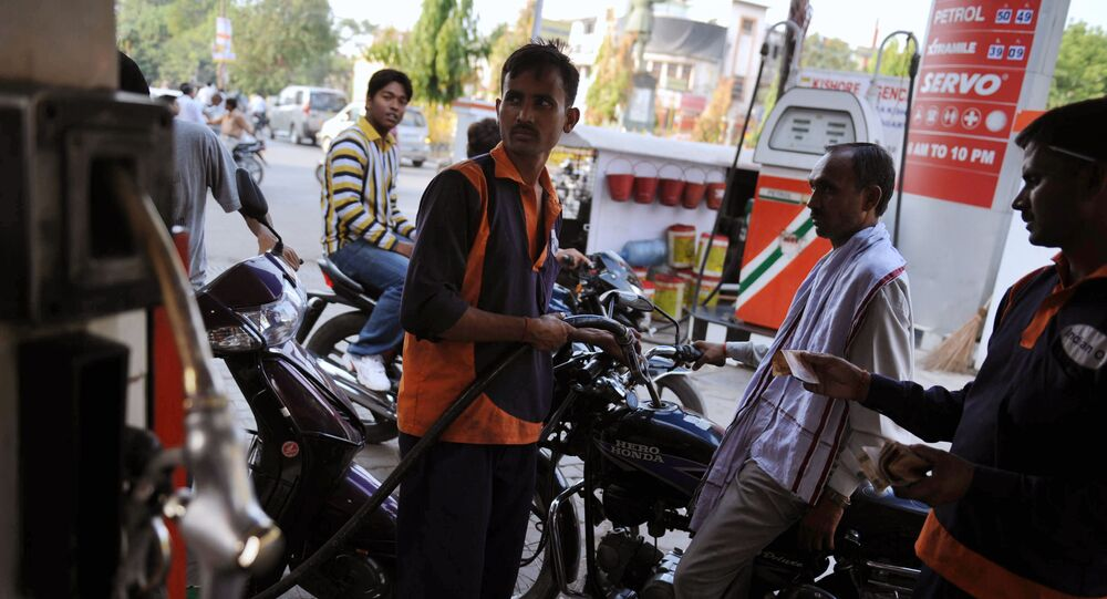 A petrol pump attendant (C, in orange) fills the fuel tank of a motorcycle in Allahabad