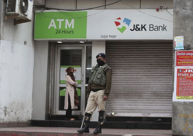 A security person stands guard outside an ATM during lockdown to prevent the spread of new coronavirus in Jammu, India, Tuesday, March 31, 2020