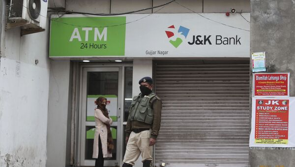A security person stands guard outside an ATM during lockdown to prevent the spread of new coronavirus in Jammu, India, Tuesday, March 31, 2020 - Sputnik International