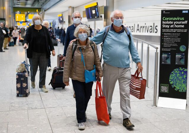 Travellers who had been aboard the Braemar cruise ship, operated by Fred Olsen Cruise Lines, and wearing face masks as a precautionary measure against covid-19, react as they arrive at Heathrow Airport in London on March 19, 2020, after being flown back from Cuba.