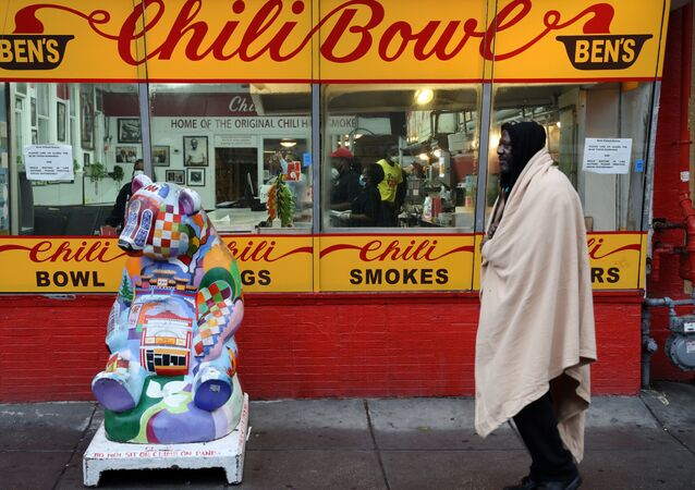 A member of the homeless community walks past Ben's Chili Bowl, whose founders Ben and Virginia Ali famously kept the restaurant running through very difficult times in the past, as the eatery navigates the coronavirus disease (COVID-19) outbreak with no seating, limited hours and help from a federal Payroll Protection Program Loan in Washington, U.S. April 30, 2020