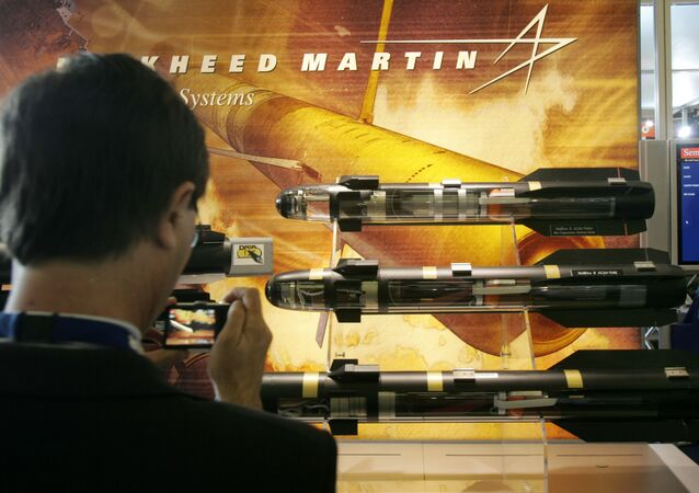 A visitor takes snapshots of models of missiles displayed in the Lockheed Martin stand, at the EuroSatory Defense Exhibition, outside Paris, Tuesday June 17, 2008.