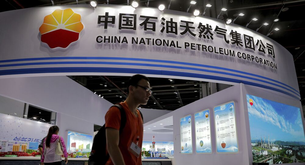 In this Sept. 21, 2016, photo, visitors walk by the China National Petroleum Corporation (CNPC) exhibition booth during the China International Chemical Industry Fair in Shanghai, China.