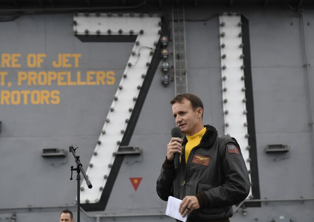 Capt. Brett Crozier, commanding officer of the aircraft carrier USS Theodore Roosevelt (CVN 71), addresses the crew during an all-hands call on the ship's flight deck