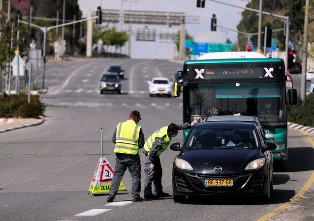 Israeli police check a driver in a car on a roadblock in a main road in Jerusalem as they try to contain the spread of the coronavirus  disease (COVID-19) from the densely populated neighborhoods where the infection rate is high, April 12, 2020.