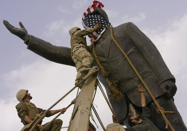 In this file photo taken Wednesday, April 9, 2003, an Iraqi man, bottom right, watches Cpl. Edward Chin of the 3rd Battalion, 4th Marines Regiment, cover the face of a statue of Saddam Hussein with an American flag before toppling the statue in downtown in Baghdad, Iraq.