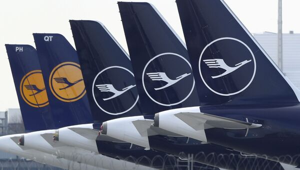 German Lufthansa planes sit parked in a line at the airport in Munich, Germany, Thursday, March 26, 2020 - Sputnik International