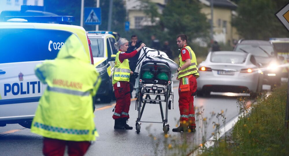 A picture taken on August 10, 2019 shows medics with a stretcher near the al-Noor islamic center mosque where a gunman, armed with multiple weapons, went on a shooting spree in the town of Baerum, an Oslo suburb