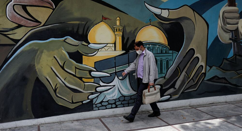 A man wearing a protective face mask walks past a Palestine mural in Tehran