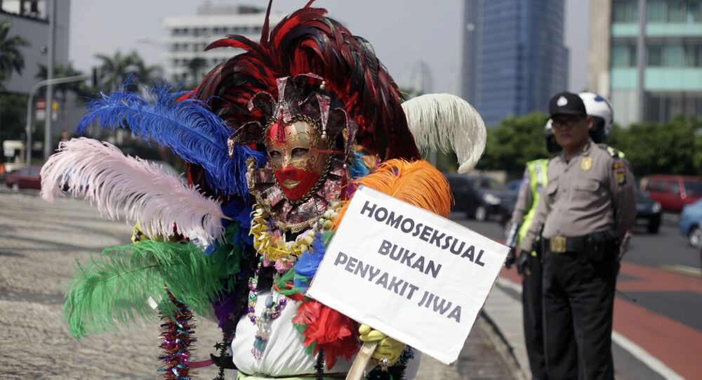 gay activist in Indonesia holds a placard that reads: Homosexuality is not mentall illness