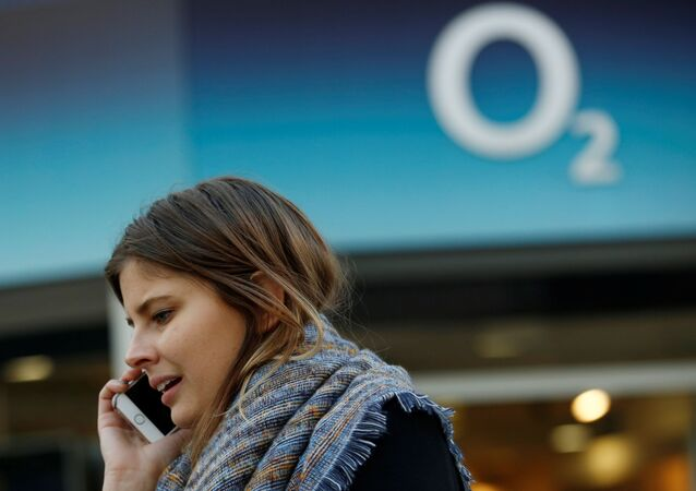A woman speaks on a mobile telephone outside an O2 store in central London