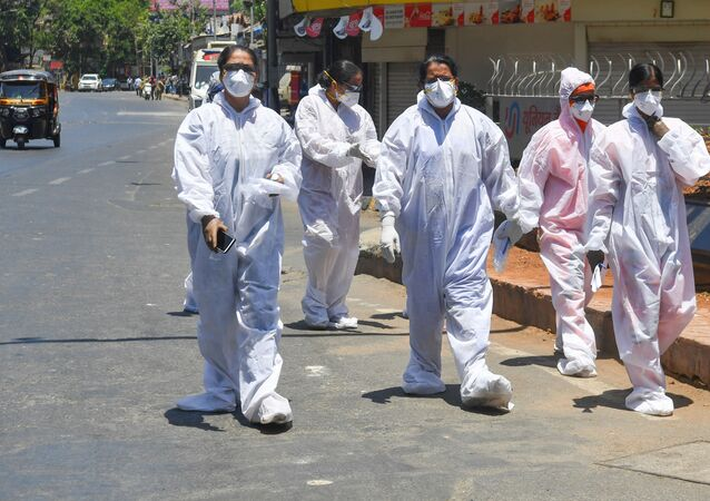 Healthcare workers wearing Personal Protective Equipment (PPE) walk out of a hospital during a government-imposed nationwide lockdown as a preventive measure against the COVID-19 coronavirus, in Mumbai on May 4, 2020.