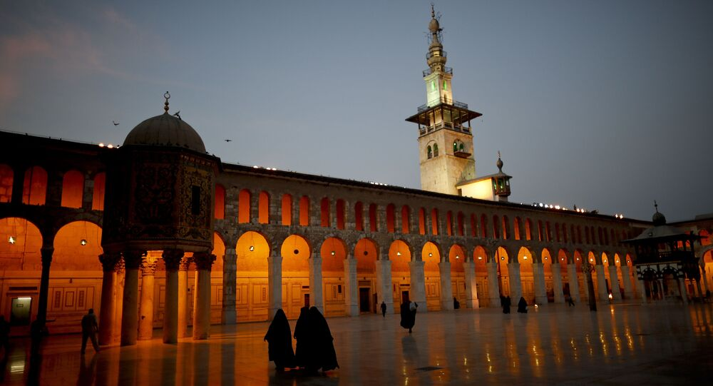 Muslim women walk in the courtyard of the 7th century Umayyad Mosque in Damascus, Syria, Wednesday, Oct. 3, 2018