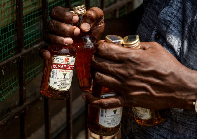 A man carries bottles of alcohol bought from a liquor shop after the government eased a nationwide lockdown imposed as a preventive measure against the COVID-19 coronavirus, on the outskirts of Chennai on May 7, 2020.