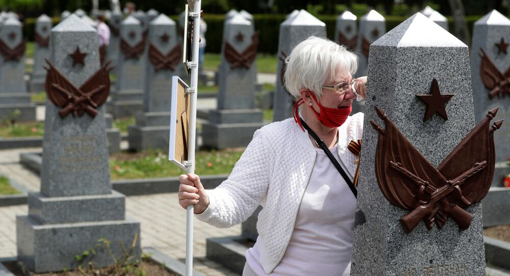 A woman mourns at a grave of a Russian soldier at the Olsany cemetery to commemorate the 75th anniversary of the end of World War Two in Prague, Czech Republic, May 8, 2020