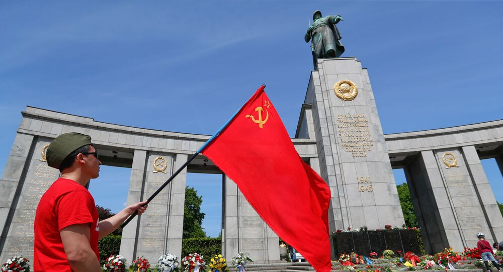 A man with a Soviet flag attends a celebration to mark Victory Day and the 75th anniversary of the end of World War Two at the Soviet War Memorial at Tiergarten Park in Berlin, Germany, May 8, 2020