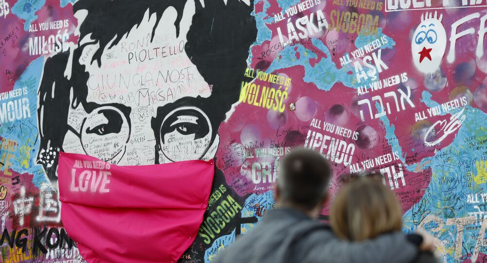 A couple look at the Lennon Wall with a face mask attached to the image of John Lennon, in Prague, Czech Republic, Monday, April 6, 2020.