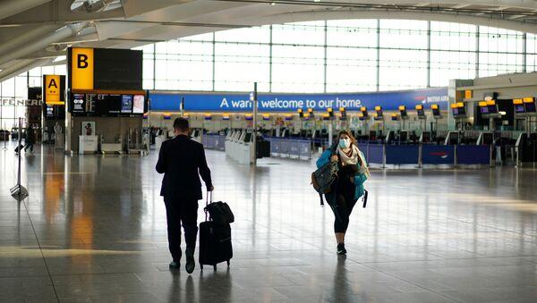 A woman wearing a mask is seen at Heathrow airport, London, Britain, April 5, 2020. - Sputnik International