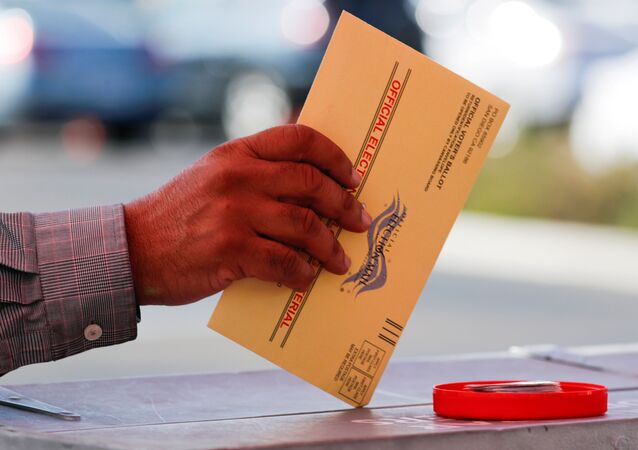 An election worker places a mail-in ballot into an election box at a drive-through drop off location at the Registrar of Voters in San Diego, California, US, 5 November 2018