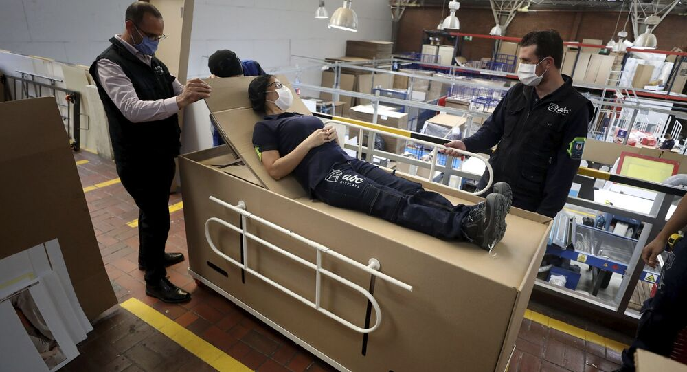 Rodolfo Gomez, left, and his employees demonstrate how their design of a cardboard box can serve as both a hospital bed and a coffin