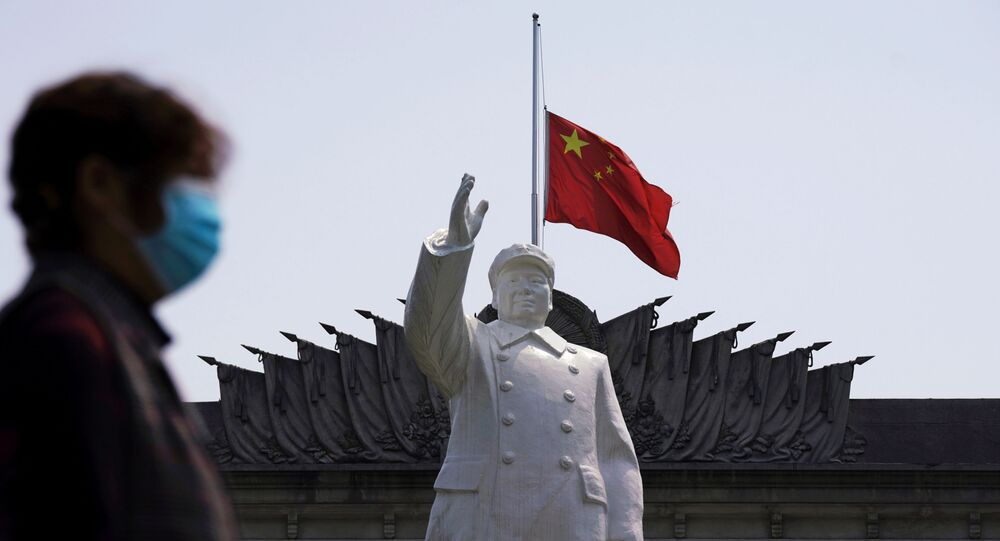 The Chinese national flag flies at half-mast behind a statue of late Chinese chairman Mao Zedong in Wuhan, Hubei province, as China holds a national mourning for those who died of the coronavirus disease (COVID-19), on the Qingming tomb-sweeping festival, April 4, 2020
