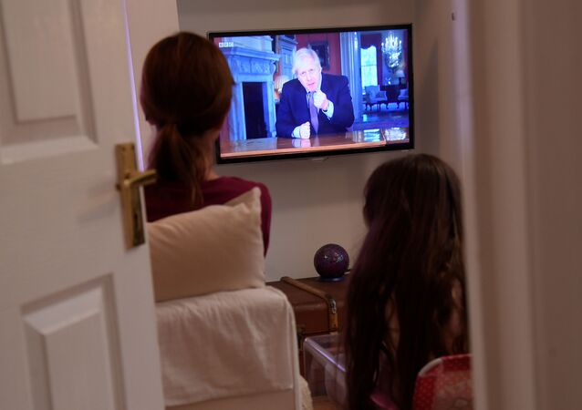 Family members in a house in London watch Britain's Prime Minister Boris Johnson on television during a broadcast to outline plans for gradually easing lockdown measures following the outbreak of the coronavirus disease (COVID-19), London, Britain, May 10, 2020